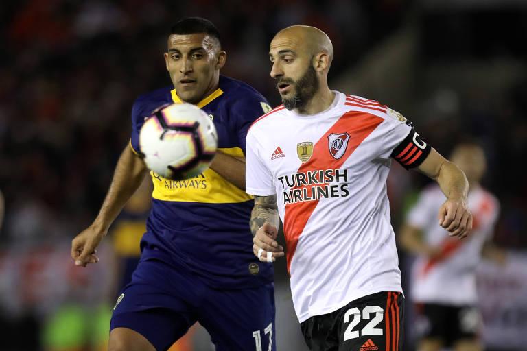Com a faixa de capitão, Pinola disputa a bola com Wanchope Ábila, do Boca Juniors