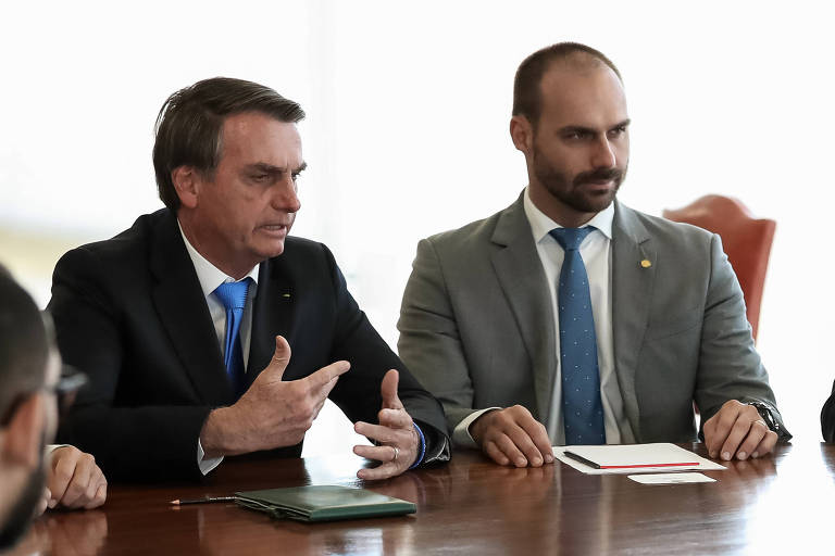 Jair e Eduardo Bolsonaro durante audiência, em agosto