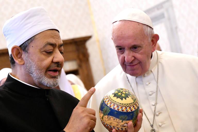 Papa olha para o presente que está nas mãos de Ahmed Al-Tayeb Sheikh; o adereço é redondo e decorado com cores amareladas e azuladas
