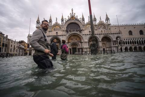 A general view shows people walking across the flooded St. Mark's Square, by St. Mark's Basilica on November 15, 2019 in Venice, two days after the city suffered its highest tide in 50 years. - Flood-hit Venice was bracing for another exceptional high tide on November 15, as Italy declared a state of emergency for the UNESCO city where perilous deluges have caused millions of euros worth of damage. (Photo by Filippo MONTEFORTE / AFP)