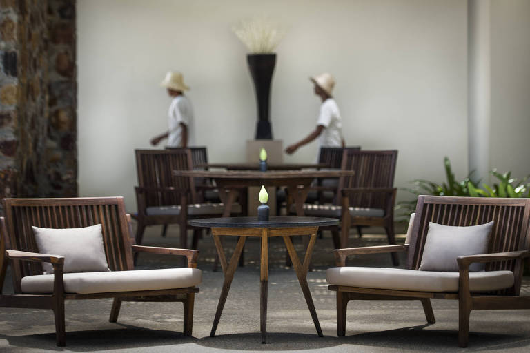 Duas cadeiras de madeira, com almofada larga no assento e pequena almofada branca no encosto.