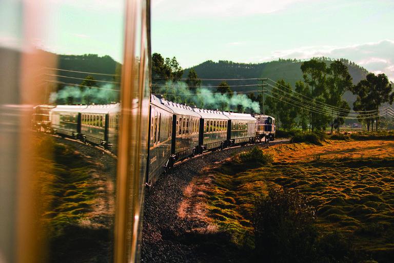 Foto tirada de dentro do trem em movimento, enquanto ele fez uma curva nos trilhos.