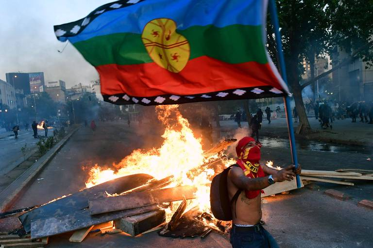 Manifestante com uma bandeira mapuche durante protesto contra o governo chileno, em Santiago