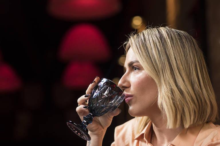 Giovanna Ewbank leva uma taça de água em direção à boca