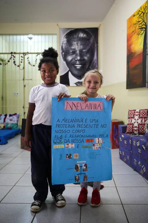 Pietra, 6, e Maria Clara, 5, alunas da escola municipal Nelson Mandela, em SP, mostram cartaz que explica a melanina,  origem da diferença de cores de pele