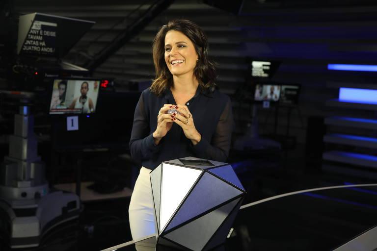 A apresentadora do Jornal da Record, Adriana Araújo, abre o papel que traz o nome de seu amigo secreto no Família Record