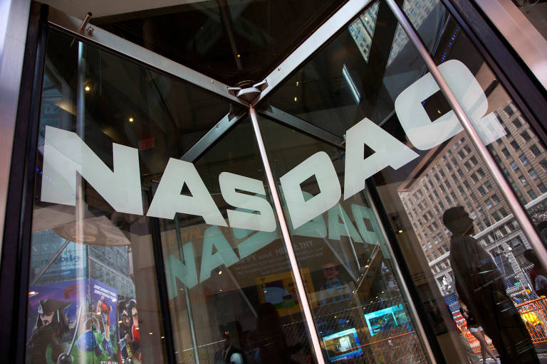 O nome da bolsa americana Nasdaq aparece em um vidro de porta giratória, o qual reflete a cidade de Nova York