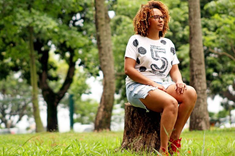 Uma mulher usando blusa branca com detalhes pretos e short azul está sentada em um tronco de árvore em meio a um parque. Ela tem cabelos encaracolados e usa óculos