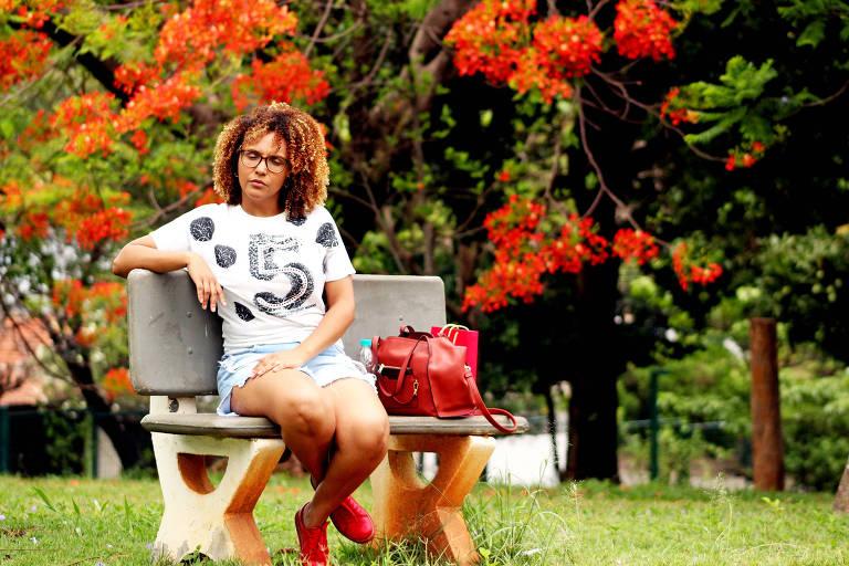 Mulher está sentada em um banco em meio a um parque; ao fundo, árvore florida em tons vermelhos. A mulher usa camiseta branca com detalhes pretos, short azul e sapatos vermelhos