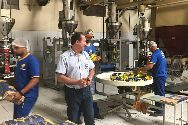 Em uma fábrica de café, o dono, vestido com uma camisa social branca e uma calça escura observa seus funcionários, uniformizados de azul, trabalhares nas sacas de café.