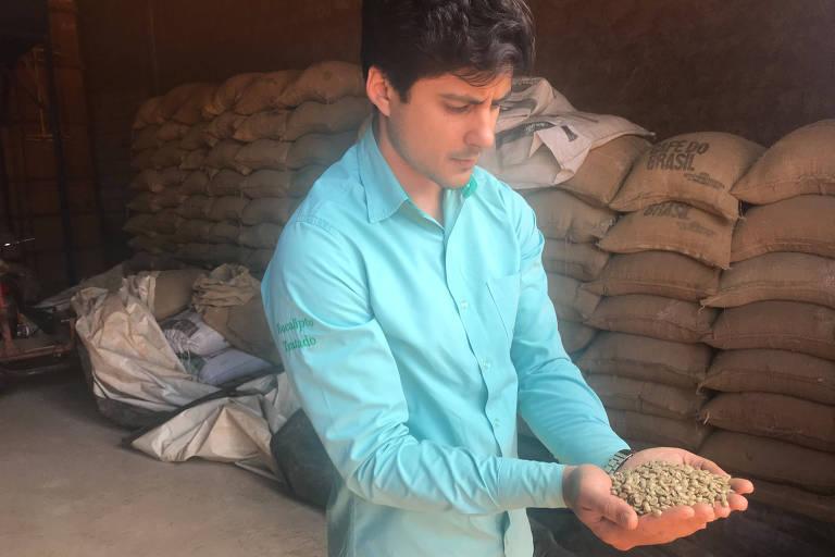 O produtor rural, vestido com uma camisa azul clara, segura vários grãos de café com as mãos unidas em concha à frente. Ao fundo, várias sacas de café.