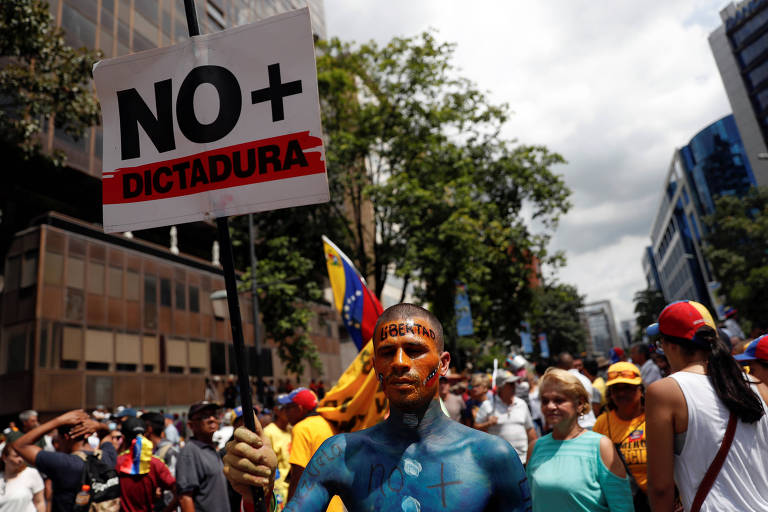 """Em meio a muitos manifestantes, homem segura carta em que se lê """"chega de ditadura"""""""