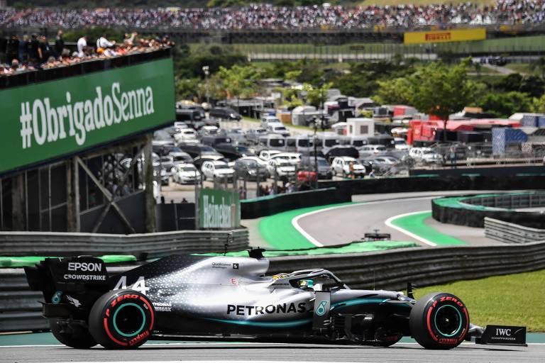 Carro de Hamilton  passa em alta velocidade em primeiro plano. No fundo da imagem, há vários carros comuns estacionados