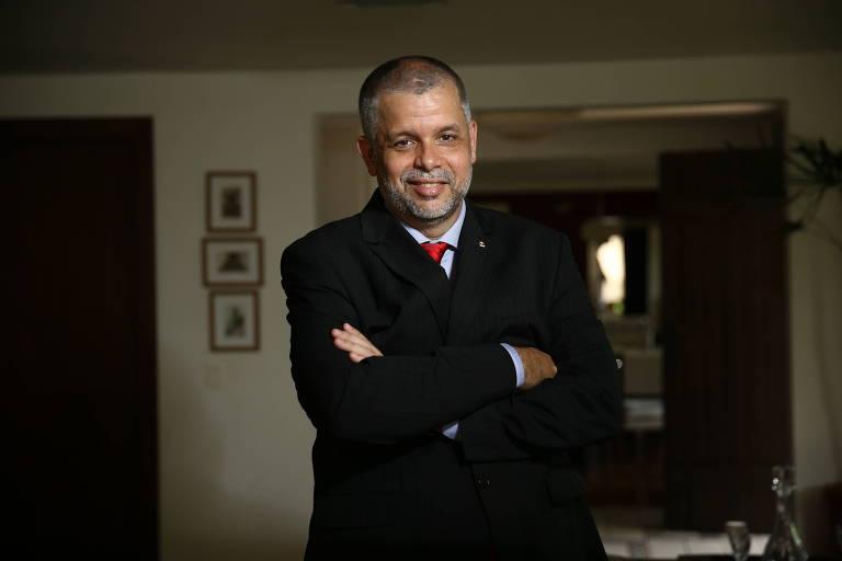 O executivo José Robalinho Cavalcanti, procurador criminal da 1a Região em Brasília, para no meio de uma sala, vestindo terno preto, camisa branca e gravata vermelha e sorri, de braços cruzados, olhando para a câmera.
