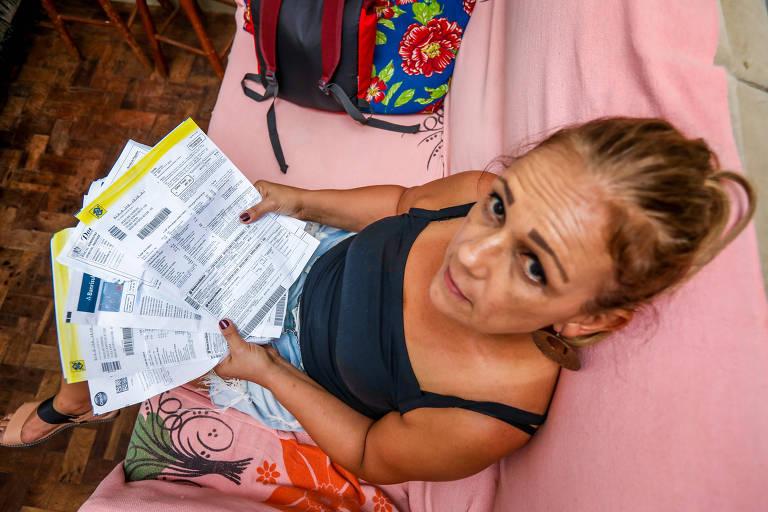 A professora Jaqueline Pontes Ferreira, da rede estadual gaúcha está sentada em um sofá rosa claro, com a câmera posicionada acima dela. Ela segura uma porção de contas não pagas e olha com expressão séria, de baixo para cima, para a câmera.