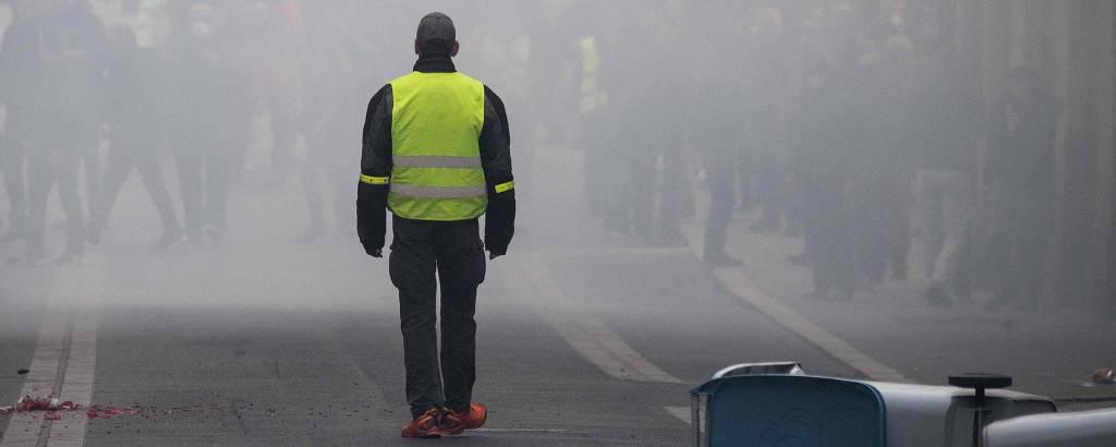 Homem protesta numa manifestação que marca um ano da revolta dos coletes amarelos na cidade de Nantes, na França