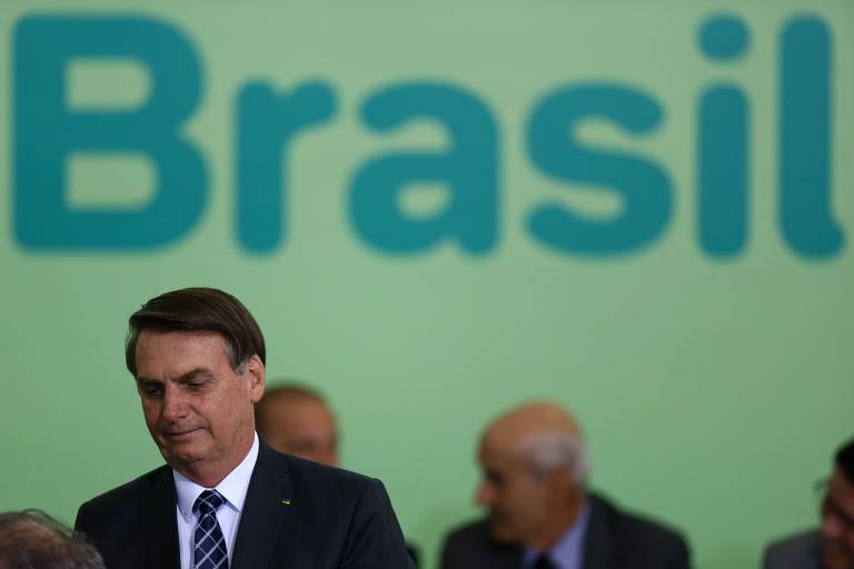 """O presidente Jair Bolsonaro está à frente, de terno, camisa e gravata. Ao fundo, é possível ver um fundo verde, com os escritos """"Brasil"""" em azul."""