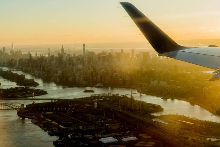 Avião no ar com cidade de Nova York ao fundo