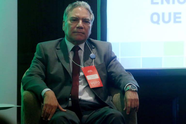 O general Marco Aurélio Vieira foi exonerado do cargo de secretário especial do Esporte em abril de 2019. Na imagem ele aparece sentado em um ambiente de palestra. Ele veste um terno cinza, uma gravata cor de vinho e um relógio na mão esquerda. Atrás dele há um telão onde é exibida uma apresentação.