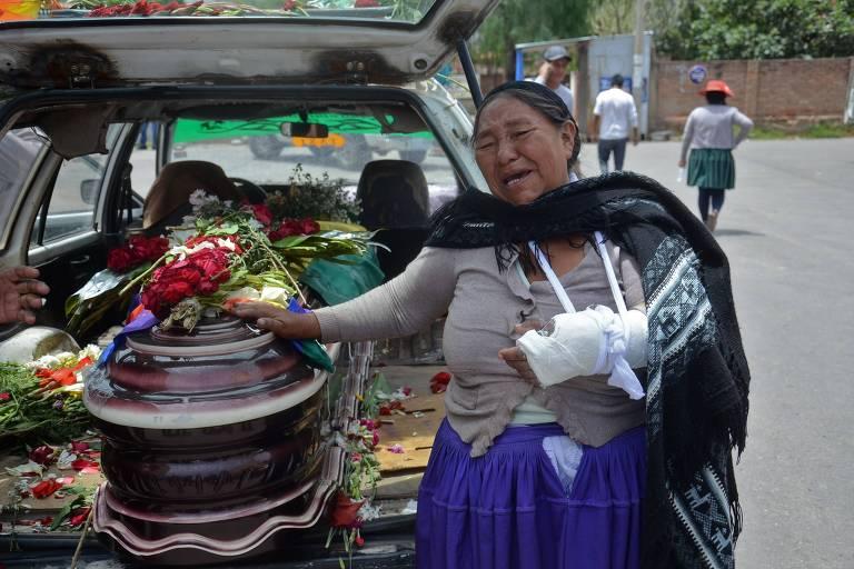Familiar chora ao lado de caixão de manifestante morto em confronto com a polícia em Cochabamba