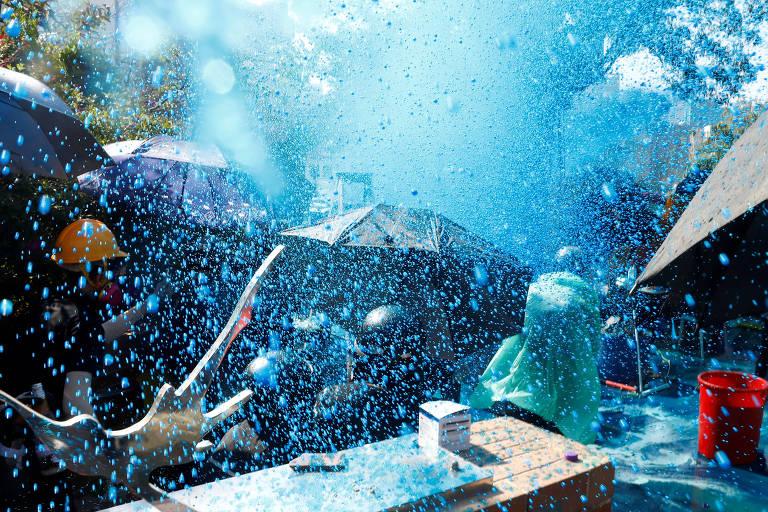Uma chuva azul vibrante atinge os manifestantes; o jato de água parece uma névoa que cobre guarda-chuvas