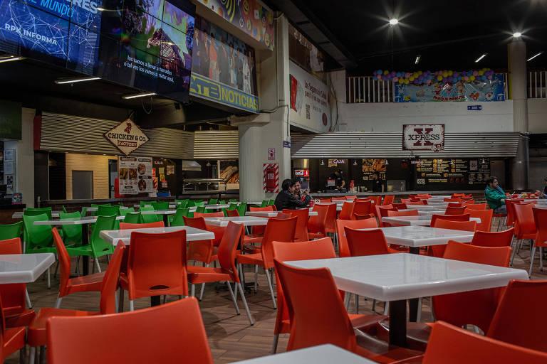 Mercado vazio, com muitas mesas e cadeiras totalmente livres. Há apenas uma pessoa no centro da praça de alimentação.