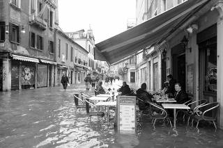 People sit at a cafe in a flooded street during a period of seasonal high water in Venice