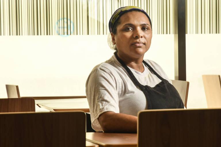 Sandra está sentada à mesa, de camiseta branca e avental preto