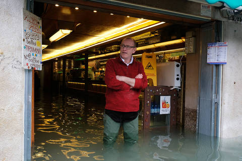 A man stands by the entrance of a restaurat during a period of seasonal high water in Venice, Italy, November 17, 2019. REUTERS/Manuel Silvestri ORG XMIT: GGG-MSL146