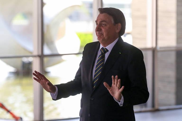 """O presidente Jair Bolsonaro está parado, de terno, camisa e gravata, com as mãos fazendo sinal de """"calma""""."""
