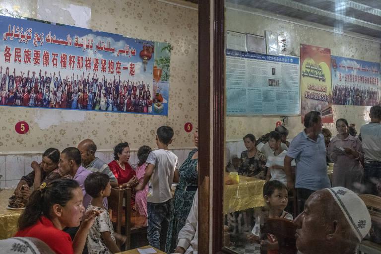 """Clientes jantam sob cartazes citando Xi Jinping, em que está escrito """"todo grupo étnico deve se unir firmemente como as sementes de uma romã"""" em restaurante em Yarkand"""