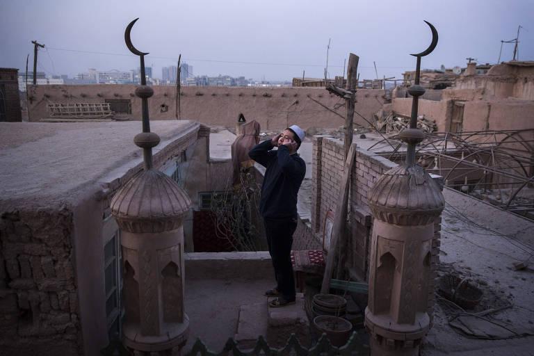 Um muezin soa o chamado à oração do telhado de uma mesquita em Kashgar, na província de Xinjiang, no oeste da China