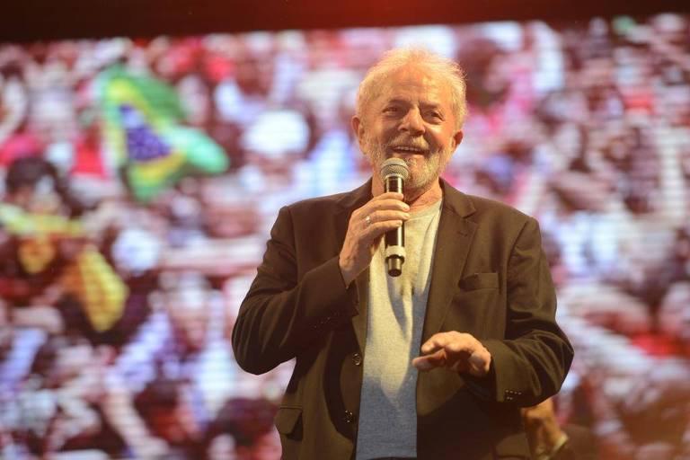 Lula segura o microfone e sorri.Ele veste um blazer preto e uma camisa cinza. Atrás, o telão mostra a plateia, majoritariamente vestida de vermelho