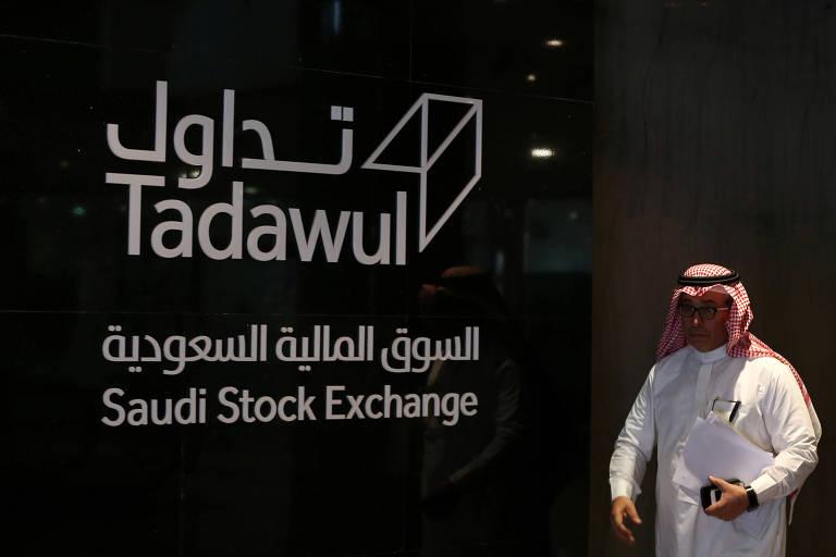 Um homem saudita caminha na frente do logo da companhia