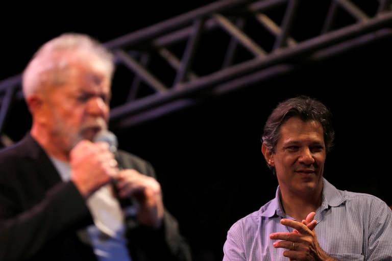 Haddad aplaude enquanto Lula, que aparece desfocado, fala ao microfone