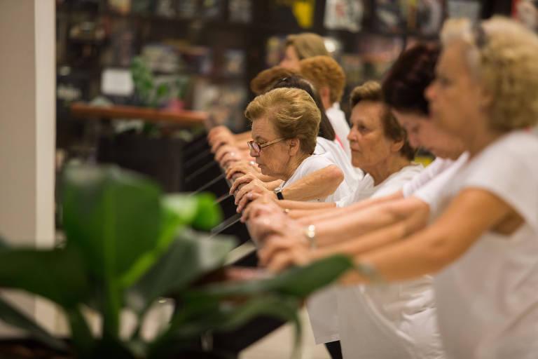 mulheres idosas vestem uniforme de ginástica e fazem exercício em um shopping; elas estão com os braços apoiados em um corrimão
