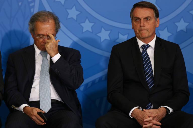 O presidente Jair Bolsonaro, está sentado ao lado do ministro Paulo Guedes, do Ministério da Economia. Paulo Guedes ajusta o óculos em um movimento sério e Bolsonaro, com as mãos cruzadas, olha à frente.