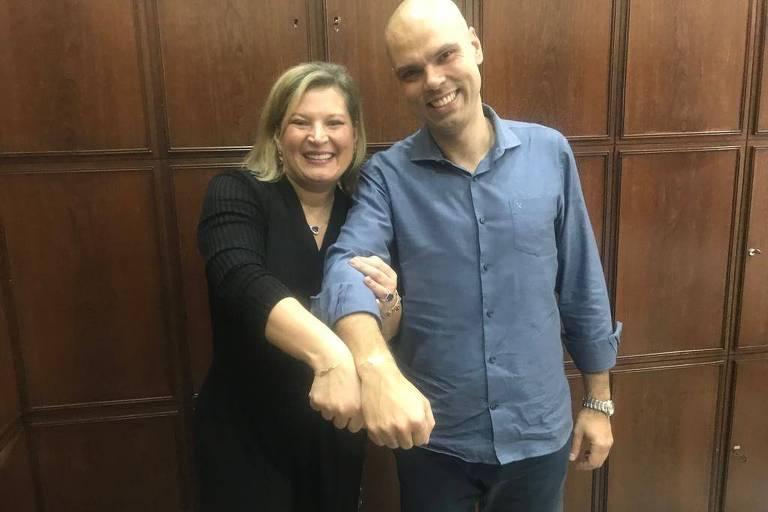 """Joice Hasselmann e Bruno Covas posam para foto, lado a lado, exibindo pulseiras com as palavras """"respeito"""" e """"força"""""""