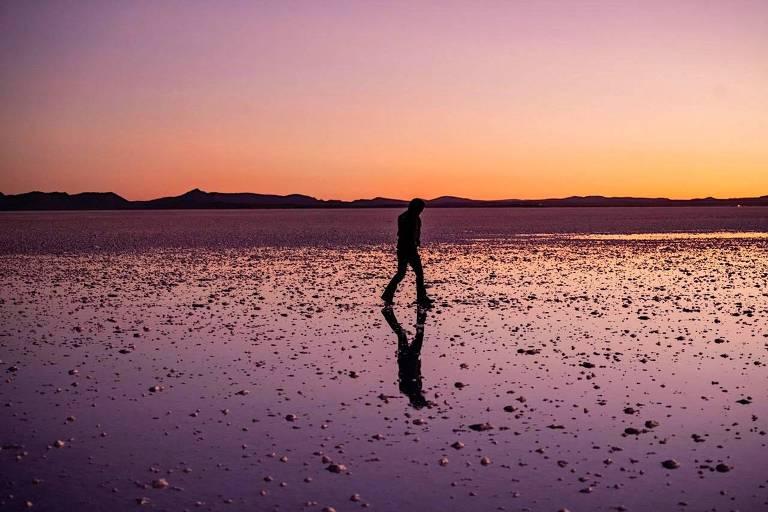 O céu e o deserto de sal têm tons laranjas, rosas e amarelos de amanhecer, uma pessoa caminha sozinha em meio a paisagem.