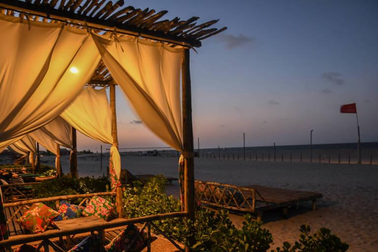 Tenda de madeira com cortinas brancas, ao entardecer, de frente para a praia.