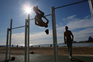 People sunbath and practice sports at the Barceloneta beach as they enjoy a sunny weather in Barcelona,