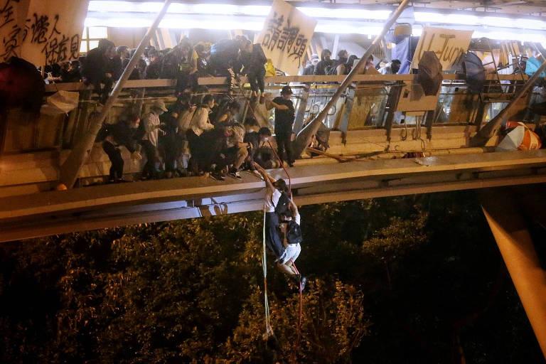Manifestante anti-governo tenta deixar a Universidade Politécnica de Hong Kong, que está cercada pela polícia, descendo de uma ponte usando uma mangueira