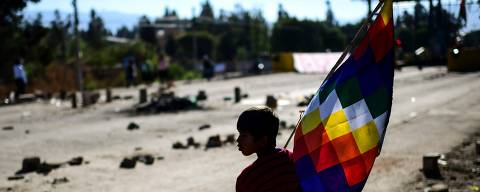 A boy holds a Wiphala flag -representing native peoples- at a road blockade set by supporters of Bolivian ex-President Evo Morales, in the outskirts of Sacaba, Chapare province, Cochabamba, on November 18, 2019. - Bolivia's interim president said Sunday she will call new elections soon, as the country struggles with violent unrest a week after the resignation of Evo Morales. (Photo by RONALDO SCHEMIDT / AFP) ORG XMIT: RSA699