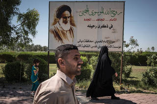 Iraqis walk past a poster of Ayatollah Ruhollah Khomeini, the founder of the Islamic Republic of Iran, in Diyala, Iraq on Sunday, June 4, 2017. (Sergey Ponomarev/The New York Times)