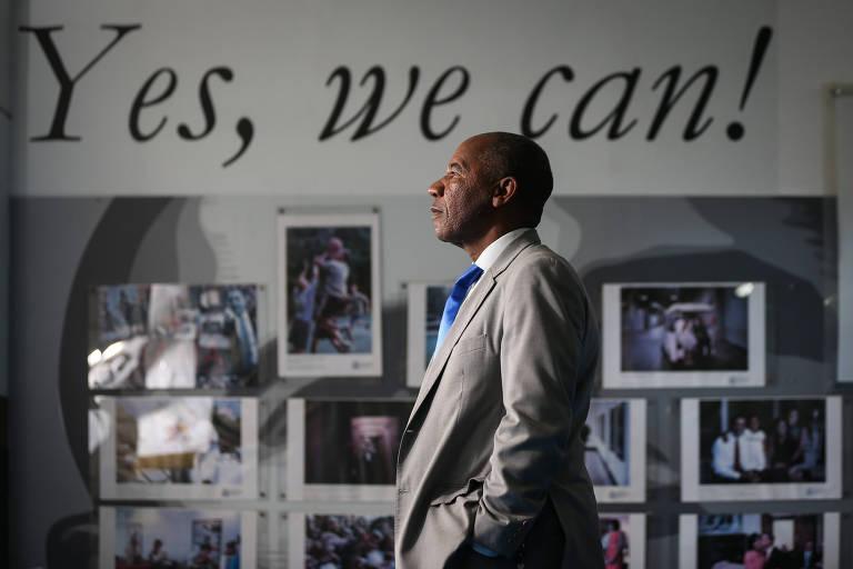 """Homem negro de terno claro e mãos no bolso posa de perfil diante de mural com os dizeres """"Yes We Can"""" e imagens de protagonistas negros"""