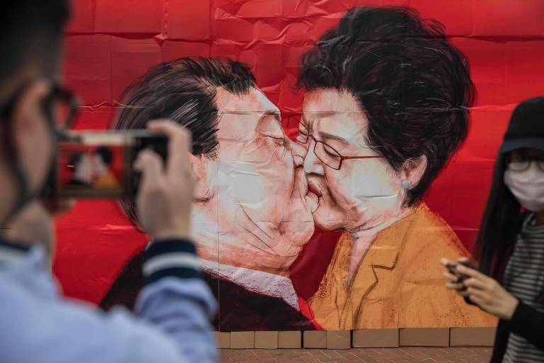 Parede com imagens do dirigente chinês, Xi Jinping, e a chefe-executiva de Hong Kong, Carrie Lam, em evento comemorando os 30 anos da queda do Muro de Berlim, em Hong Kong
