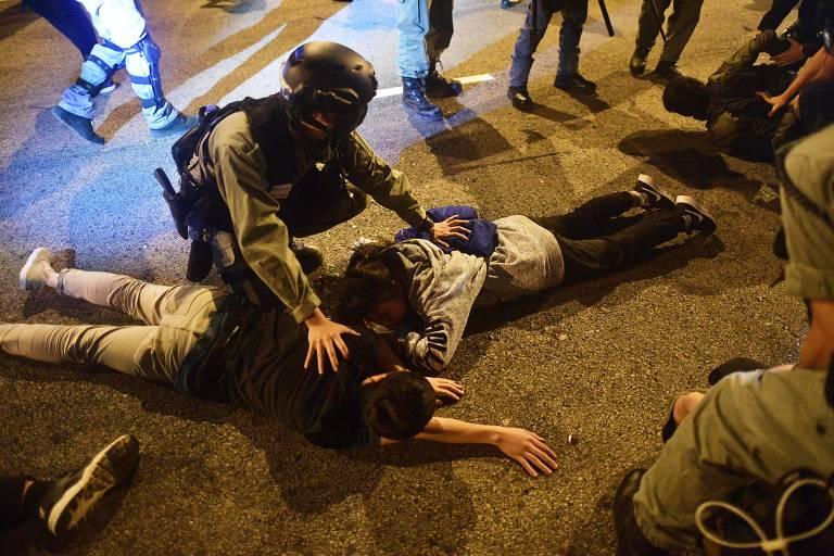 Policial prende manifestantes que tentaram fugir da Universidade Politécnica de Hong Kong