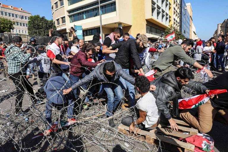 Manifestantes fogem de forças de segurança durante protesto antigoverno em Beirute