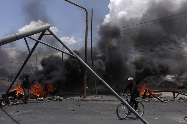 Ciclista passa por refinaria com entradas bloqueadas por pneus em chamas em El Alto, cidade vizinha a La Paz