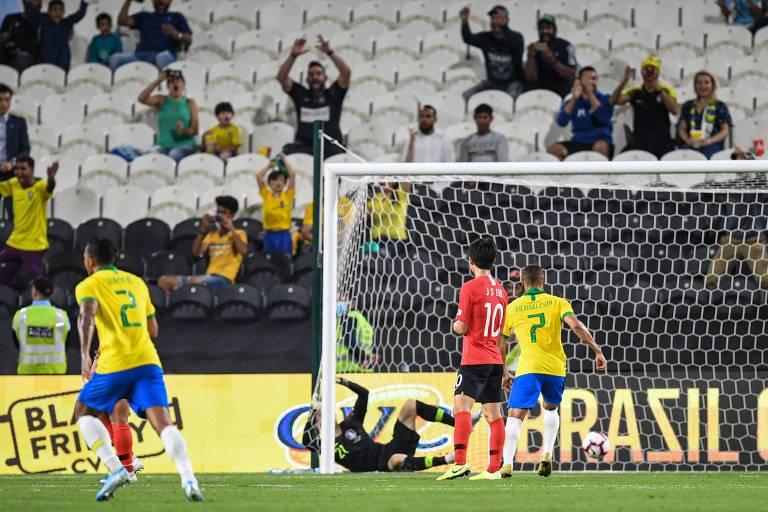 Goleiro sul-coreano Kim Seung-gyu cai dentro do gol após falhar na defesa da cobrança de falta de Philippe Coutinho; na arquibancada, poucos torcedores...